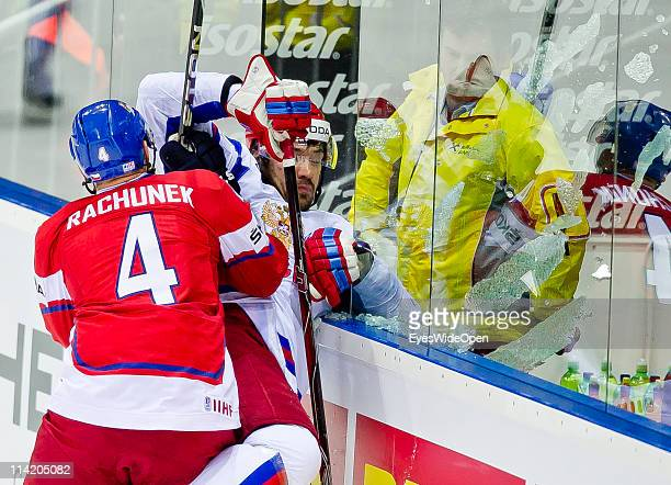 Karel Rachunek of Czech Republic tackles Yevgeni Artyukhin of Russia and breaks the safety glass during the IIHF World Championship bronze medal...
