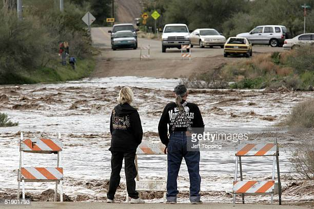 Karen and Larry Trimboli watch the rushing Agua Fria River on Squaw Valley Road December 29 2004 in Black Canyon City Arizona 50 miles north of...