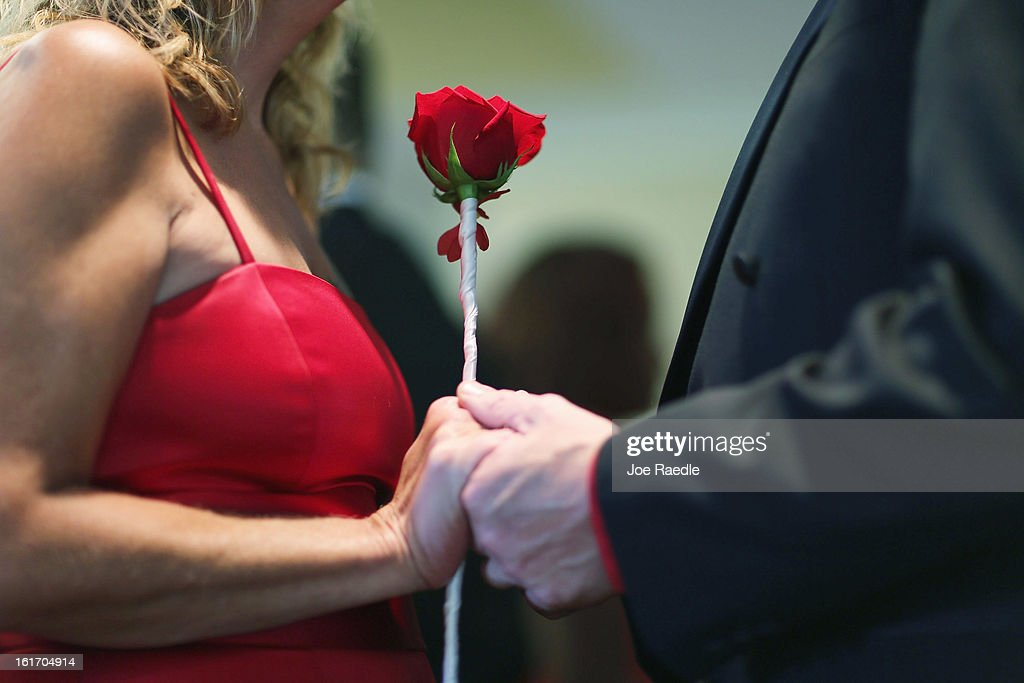Karen Brown (L) and Douglas Brown hold hands as they are wed during a group Valentine's day wedding at the National Croquet Center on February 14, 2013 in West Palm Beach, Florida. The group wedding ceremony is put on by the Palm Beach Country Clerk & Comptroller's office and approximately 40 couples tied the knot.