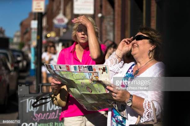 Karen Cleary left and Jackie Soares consult a Greater Portland Discovery Map map from the corner of Fore and Union streets in an effort to find a...