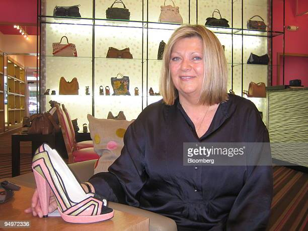 Karen Daskas owner of Tender a specialty boutique poses for a portrait with a Chrissie Morris high heel made from pink stingray's leather green...