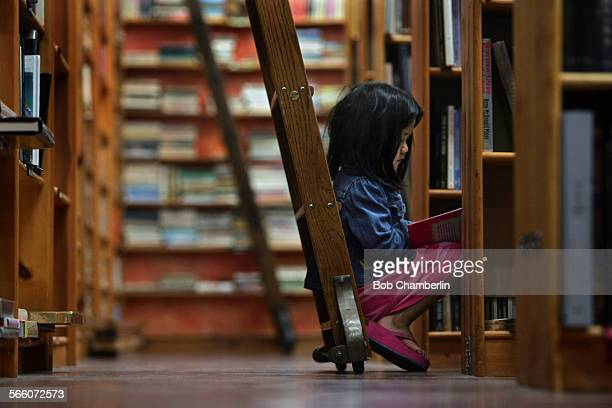 Karen David sits amid the bookshelves reading a children's book as her father Dan looks for religious books at Illiad bookstore on FEBRUARY 25 2010...