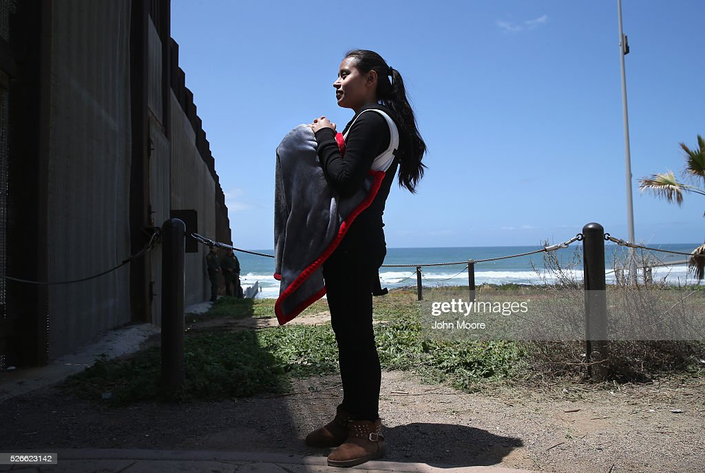 Karen Herrera, 23, holds her baby Ivan, 3 months, while speaking with family members through the U.S.-Mexico border fence on April 30, 2016 in San Diego, California. She said she has been living in California for 1 year, having applied for political asylum after her husband was murdered in Tijuana. Five families, with some members living in Mexico and others in the United States, were permitted to meet and embrace for three minutes each at a door in the fence, which the U.S. Border Patrol opened to celebrate Mexican Children's Day. It was only the third time the fence, which separates San Diego from Tijuana, had been opened for families to briefly reunite. The event was planned by the immigrant advocacy group Border Angels.