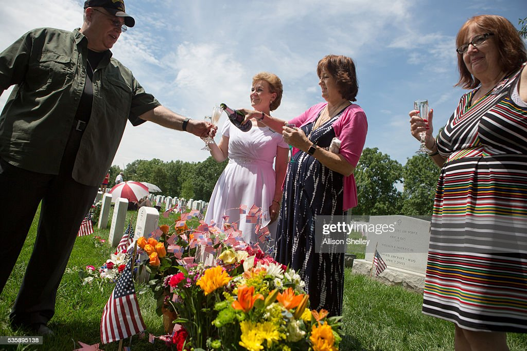 Karen Meredith of Mountain View, California, pours champagne for a friend as Vickie Castro, left, and Cathy Patton, a retired military nurse, join her around the grave of Meredith's son/Patton's nephew Lt. Kenneth Ballard in Section 60, the burial ground for military personnel killed since 2001, at Arlington National Cemetery on May 30, 2016 in Arlington, Virginia. Both Ballard and Castro's son Jonathan were killed in Iraq in 2004. The women have been gathering with others at the grave every year since to celebrate their lives.