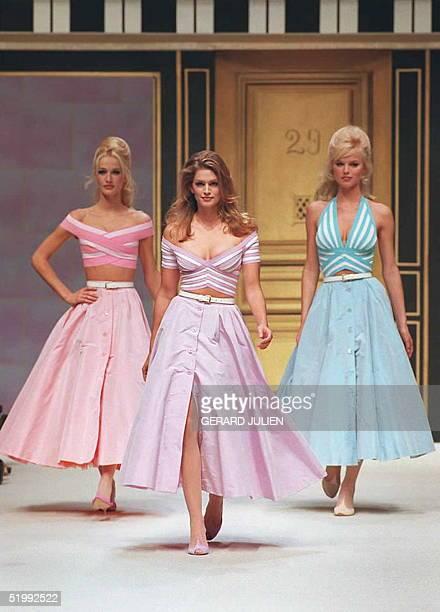 Karen Mulder Cindy Crawford and Eva Herzigova wear crisscrossed striped tops over wide front buttoned dresses in pastel for Herve Leger's...