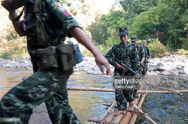 Karen National Liberation Army guerrillas in charge of the security of a team of the relief group Free Burma Rangers walk along a river on their way...