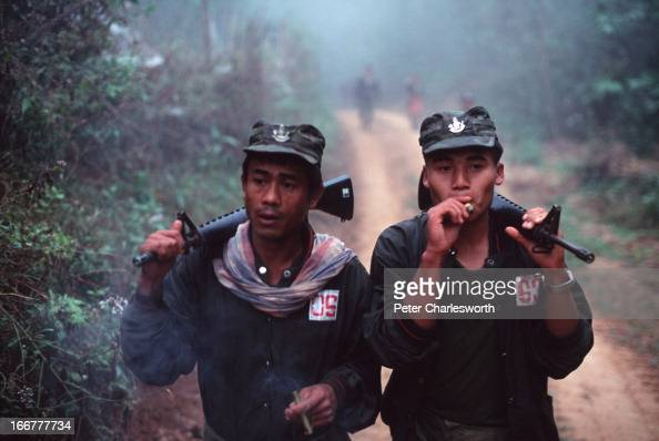 Karen National Liberation Army soldiers smoking Burmese cheroots head out on patrol from their Manerplaw stronghold on the banks of the Salween River...