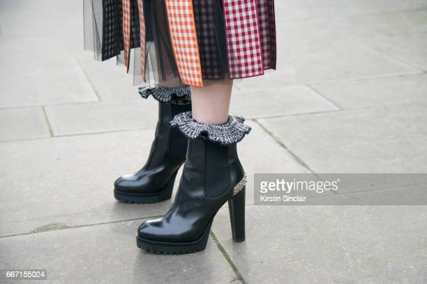 Karen Ng wears a Christopher Kane skirt and Alexander McQueen boots on day 4 of London Womens Fashion Week Autumn/Winter 2017 on February 20 2017 in...
