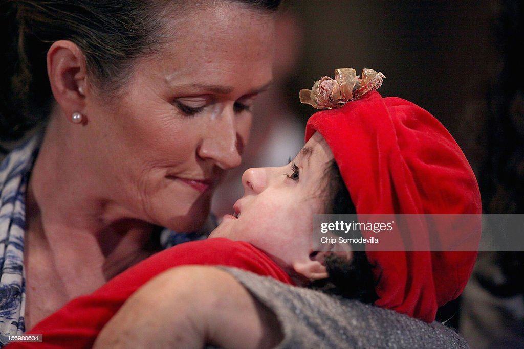 Karen Santorum (L), wife of former GOP presidential candidate and former Sen. Rick Santorum (R-PA), cradles her daughter, Isabella, while participating in a news conference opposing the United Nations Convention on the Rights of Persons with Disabilities at the Dirksen Senate Office Building on Capitol Hill November 26, 2012 in Washington, DC. In 2008 the Santorum's eighth child, Isabella, was born and diagnosed with Edwards syndrome (Trisomy 18), a serious genetic disorder, with only a 10% chance of survival past one year old. Following the second hospitalization of Isabella in a few months, Santorum officially suspended his campaign for the presidency in June of 2012.
