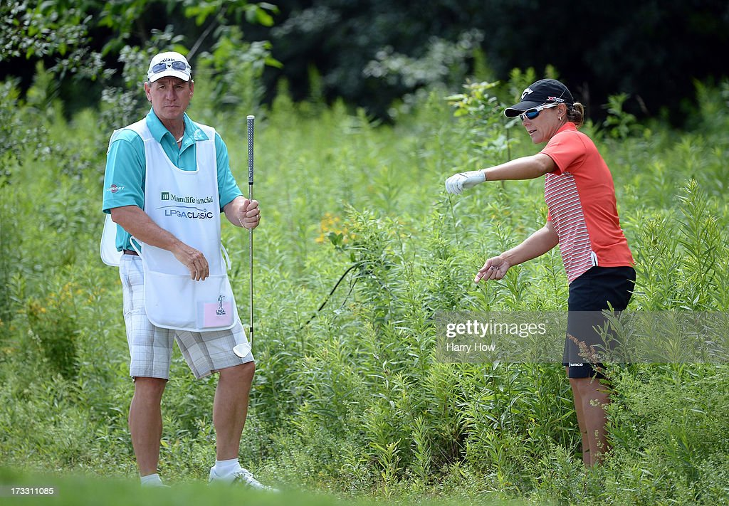 Karen Stupples of England and her caddie line up a shot from the rough of the 11th hole during round one of the Manulife Financial LPGA Classic at the Grey Silo Golf Course on July 11, 2013 in Waterloo, Canada.