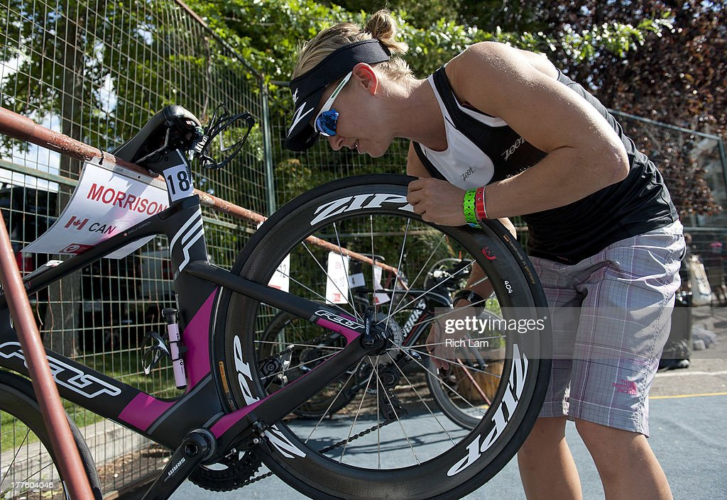 Karen Thibideau of Canada adjusts the rear wheel on her bike after racking it during the Challenge Penticton Triathlon previews on August 24, 2013 in Penticton, British Columbia, Canada.