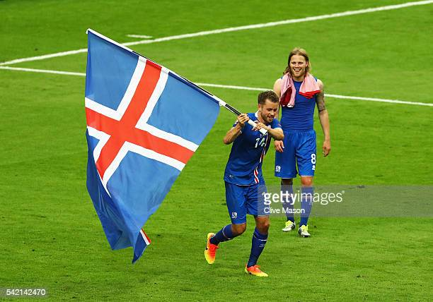 Kari Arnason of Iceland celebrates with his national flag after victory in the UEFA EURO 2016 Group F match between Iceland and Austria at Stade de...
