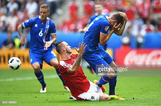 Kari Arnason of Iceland holds his head after a challenge by Marko Arnautovic of Austria during the UEFA EURO 2016 Group F match between Iceland and...