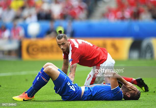 Kari Arnason of Iceland lies down in pain after a challenge by Marko Arnautovic of Austria during the UEFA EURO 2016 Group F match between Iceland...