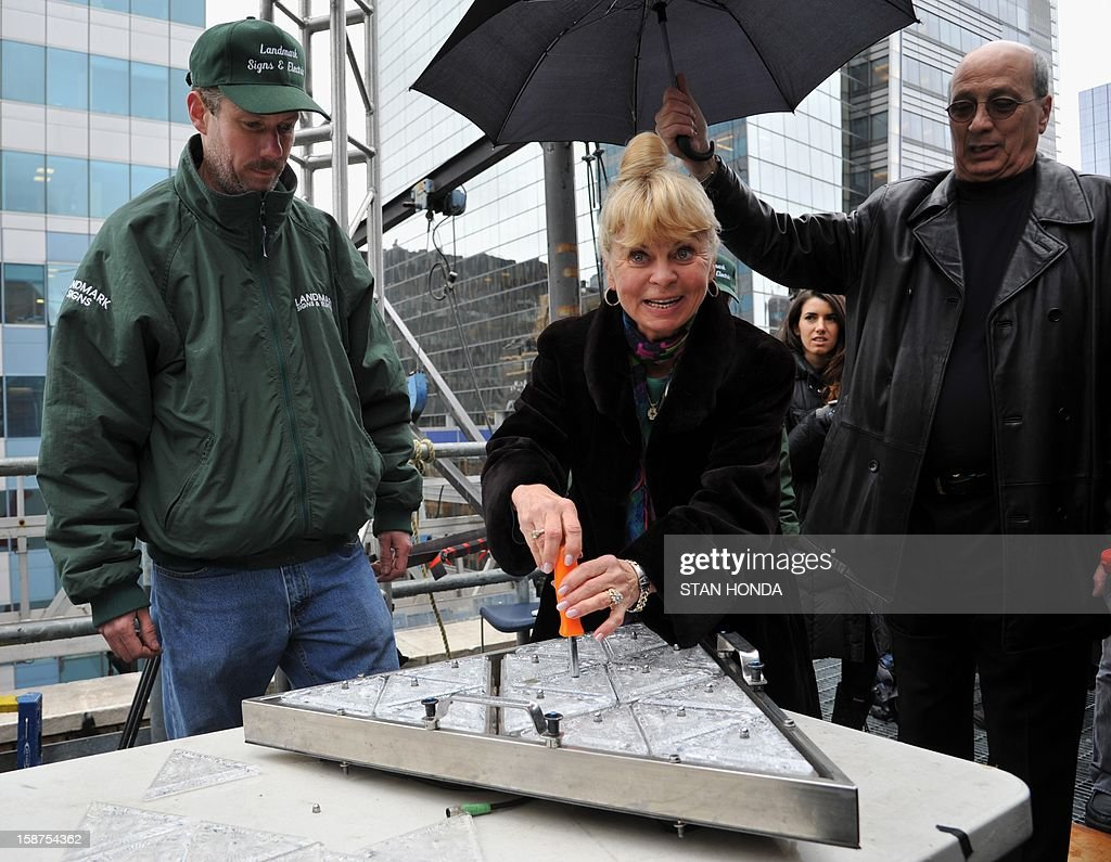 Kari Clark, widow of television broadcaser Dick Clark, helps install a Waterford Crystal triangle onto a panel for the Times Square New Year's Eve ball on December 27, 2012 in New York. Dick Clark was a longetime televison host of the Times Square New Year's Eve ball drop. For this year's ball 288 new triangles, which are lighted from behind, were installed. AFP PHOTO/Stan HONDA