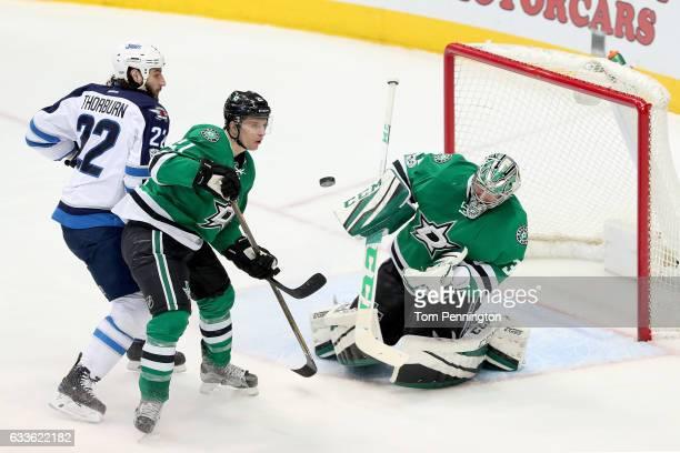 Kari Lehtonen of the Dallas Stars blocks a shot on goal against Chris Thorburn of the Winnipeg Jets and Antoine Roussel of the Dallas Stars defends...