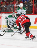 Kari Lehtonen of the Dallas Stars makes a save against Matt Kassian of the Ottawa Senators as Jordie Benn tries to block the shot at Canadian Tire...