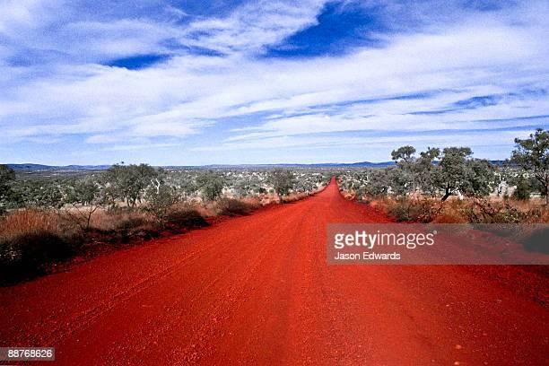 A rich red volcanic track runs straight across the desert plain.
