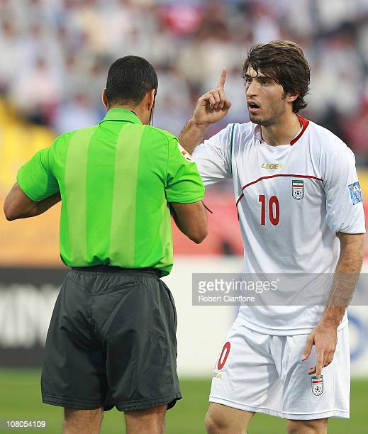 Karim Ansarifard of Iran argues with referee Nawaf Shukralla of Bahrain during the AFC Asian Cup Group D match between DPR Korea and Iran at Qatar...