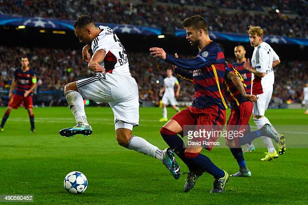 Karim Ballarabi of Bayer 04 Leverkusen competes for the ball with Gerard Pique of FC Barcelona during the UEFA Champions League Group E match between...
