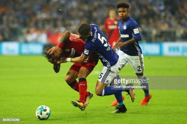 Karim Bellarabi of Bayer 04 Leverkusen is tackled and fould by Matija Nastasic of Schalke 04 during the Bundesliga match between FC Schalke 04 and...
