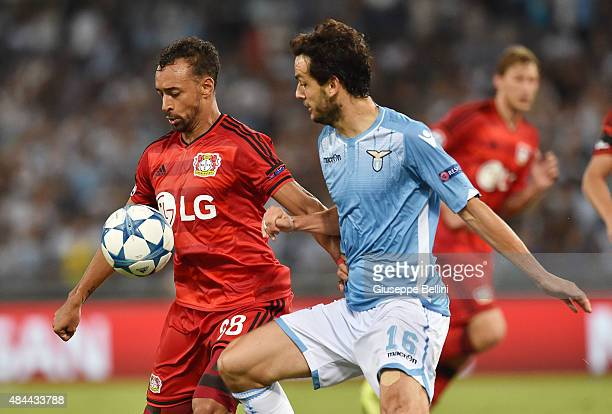 Karim Bellarabi of Bayer Leverkusen and Marco Parolo of SS Lazio in action during the UEFA Champions League qualifying round play off first leg match...