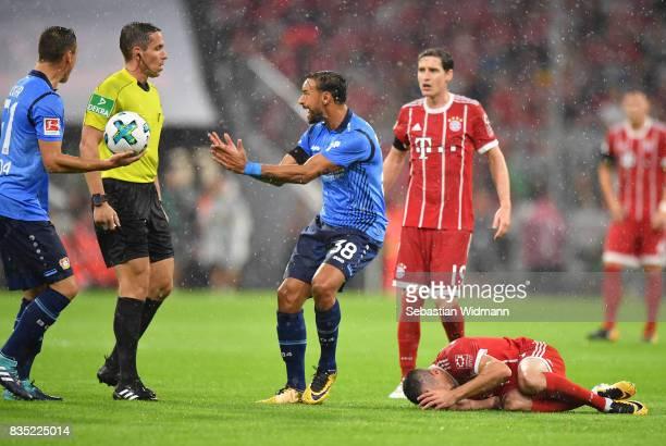 Karim Bellarabi of Bayer Leverkusen argues with referee Tobias Stieler while Franck Ribery of Bayern Muenchen lies on the pitch during the Bundesliga...