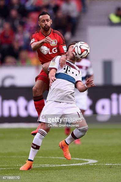 Karim Bellarabi of Bayer Leverkusen challenges Mario Goetze of FC Bayern Muenchen during the Bundesliga match between Bayer 04 Leverkusen and FC...