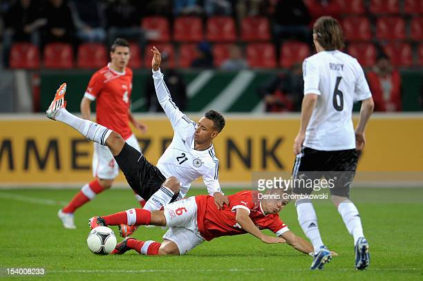 Karim Bellarabi of Germany and Amir Abrashi of Switzerland battle for the ball during the Under 21 European Championship Play Off match between...