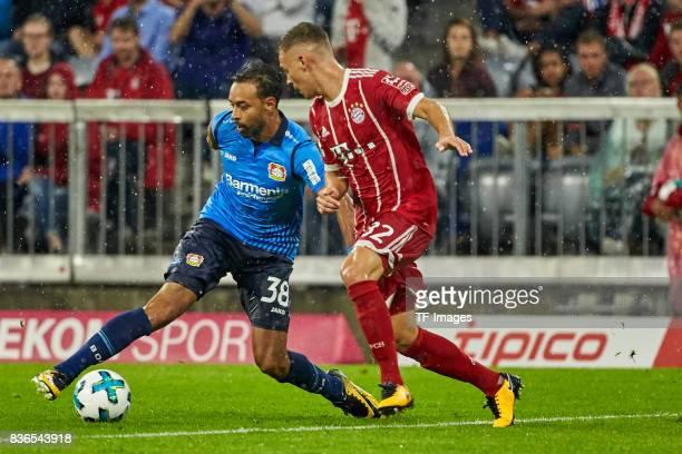 Karim Bellarabi of Leverkusen and Joshua Kimmich of Muenchen battle for the ball during the Bundesliga match between FC Bayern Muenchen and Bayer 04...