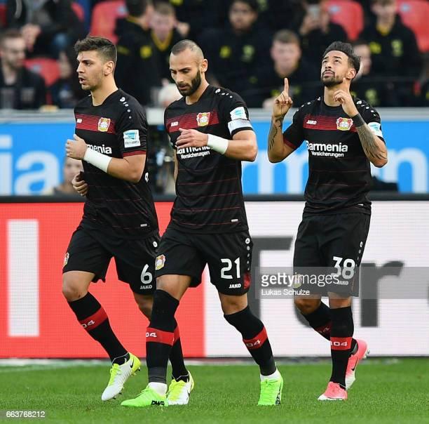 Karim Bellarabi of Leverkusen celebrates scoring the first goal with Aleksandar Dragovic and Ömer Toprak during the Bundesliga match between Bayer 04...