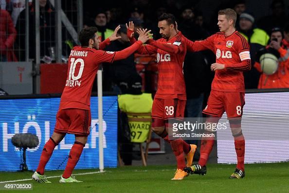 Karim Bellarabi of Leverkusen celebrates with team mate Hakan Calhanoglu and Lars Bender after scoring his team's first goal during the Bundesliga...