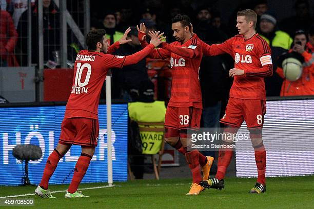 Karim Bellarabi of Leverkusen celebrates with team mate Hakan Calhanoglu and Lars Bender after scoring his team's first goal during the Bundesliga...