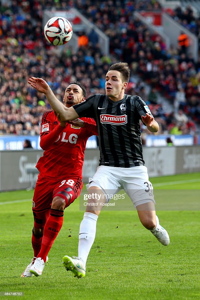 Karim Bellarabi of Leverkusen challenges Christian Guenter of Freiburg during the Bundesliga match between Bayer 04 Leverkusen and SC Freiburg at BayArena on February 28, 2015 in Leverkusen, Germany.