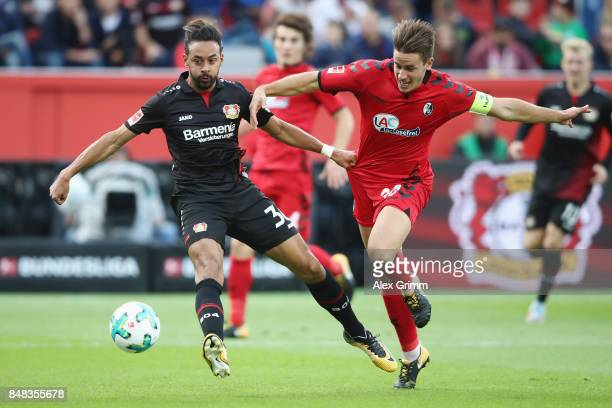 Karim Bellarabi of Leverkusen is challenged by Christian Guenter of Freiburg during the Bundesliga match between Bayer 04 Leverkusen and SC Freiburg...