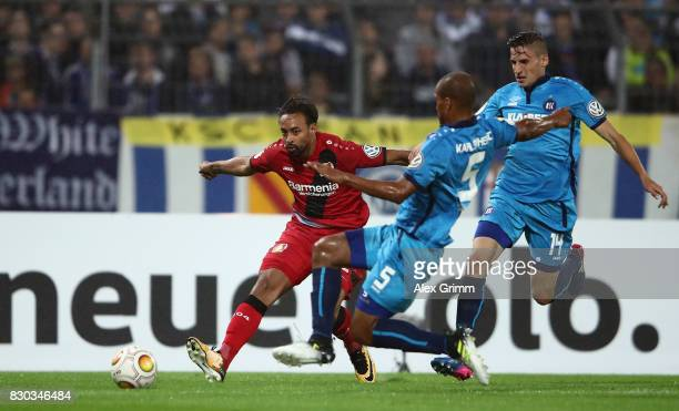 Karim Bellarabi of Leverkusen is challenged by David Pisot and Alexander Siebeck of Karlsruhe during the DFB Cup first round match between Karlsruher...
