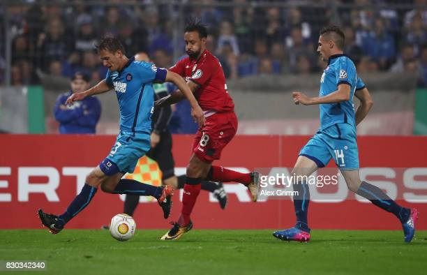 Karim Bellarabi of Leverkusen is challenged by Kai Buelow and Alexander Siebeck of Karlsruhe during the DFB Cup first round match between Karlsruher...