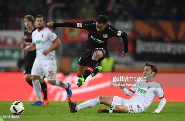 Karim Bellarabi of Leverkusen is challenged by Takashi Usami of Augsburg during the Bundesliga match between FC Augsburg and Bayer 04 Leverkusen at...