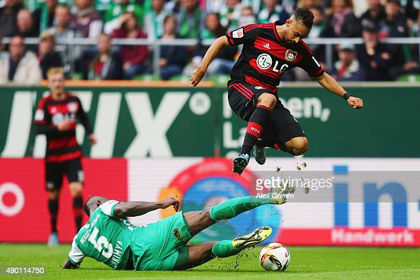 Karim Bellarabi of Leverkusen jumps over Assani Lukimya of Bremen during the Bundesliga match between Werder Bremen and Bayer Leverkusen at...
