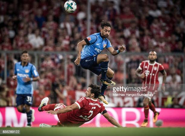Karim Bellarabi of Leverkusen jumps over Mats Hummels of FC Bayern Muenchen during the Bundesliga match between FC Bayern Muenchen and Bayer 04...
