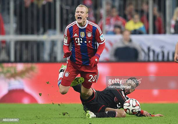 Karim Bellarabi of Leverkusen tackles Sebastian Rode of Muenchen for a yellow card during the Bundesliga match between FC Bayern Muenchen and Bayer...