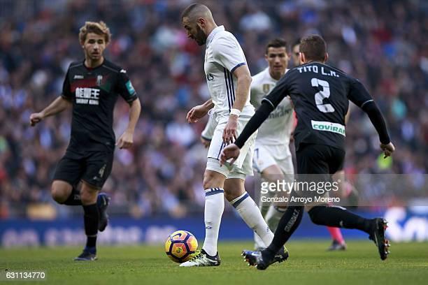 Karim Benzema competes for the ball with Roberto Romn Triguero alias Tito of Granada CF and his teammate Sergi Samper during the La Liga match...