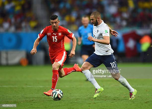 Karim Benzema of France and Blerim Dzemaili of Switzerland compete for the ball during the 2014 FIFA World Cup Brazil Group E match between...