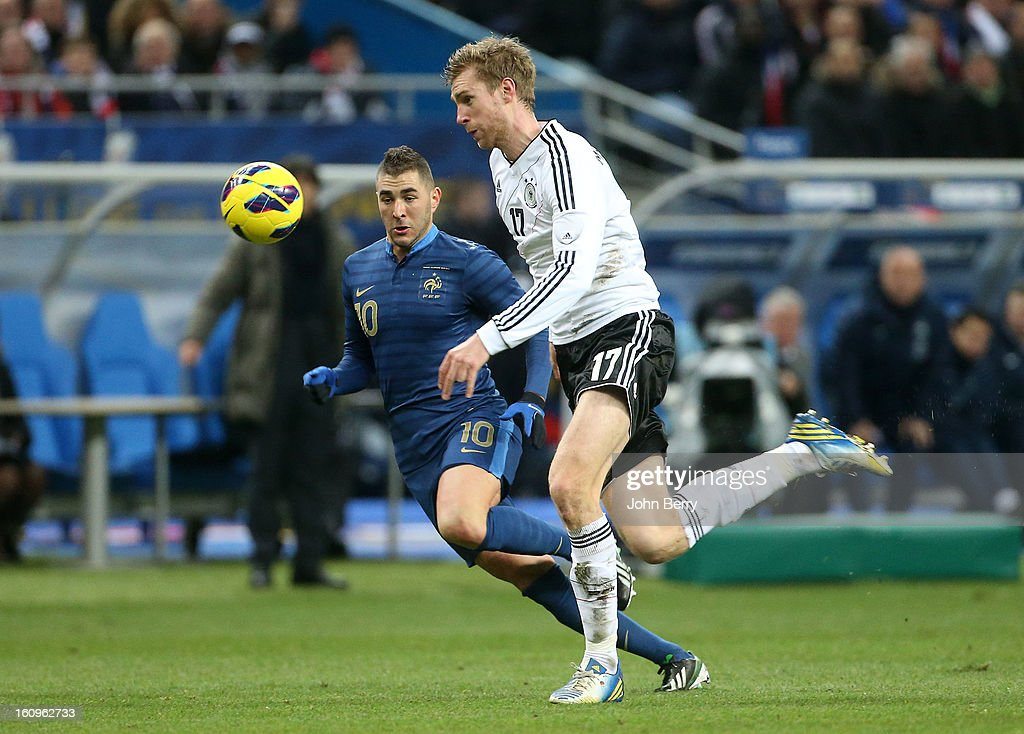 Karim Benzema of France and Per Mertesacker of Germany in action during the international friendly match between France and Germany at the Stade de France on February 6, 2013 in Paris, France.