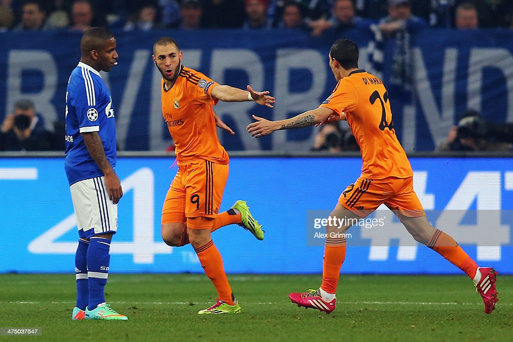 Karim Benzema of Madrid celebrates his team's first goal with team mate Angel Di Maria as Jefferson Farfan of Schalke reacts during the UEFA...