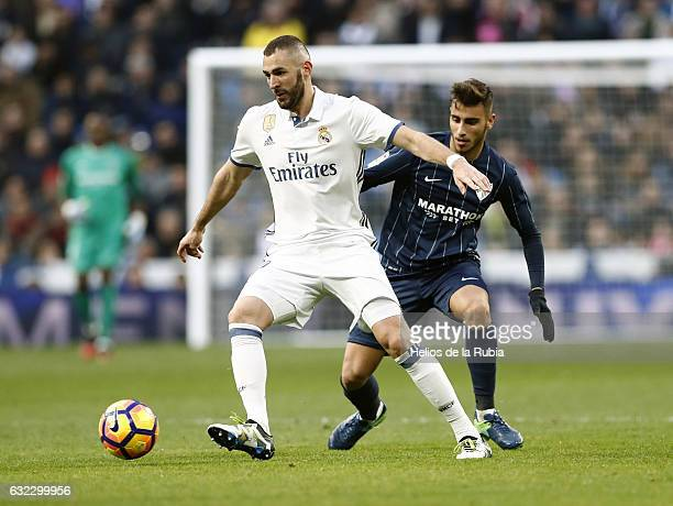 Karim Benzema of Real Madrid and Juanpi of Malaga CF compete for the ball during the La Liga match between Real Madrid and Malaga CF at Estadio...