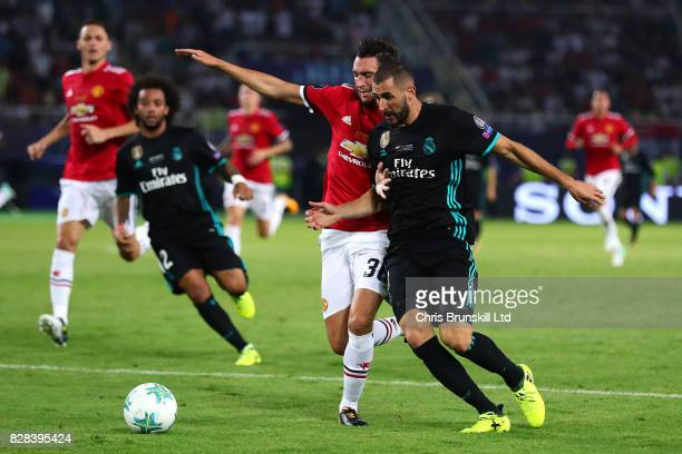 Karim Benzema of Real Madrid attempts to run past Matteo Darmian of Manchester United during the UEFA Super Cup match between Real Madrid and...
