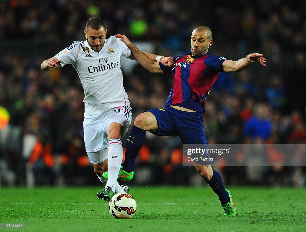 Karim Benzema of Real Madrid CF battles with Javier Mascherano of Barcelona during the La Liga match between FC Barcelona and Real Madrid CF at Camp...