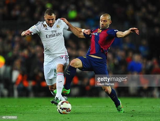Karim Benzema of Real Madrid CF battles with Javier Mascherano of Barcelona during the La Liga match between FC Barcelona and Real Madrid CF at Camp...