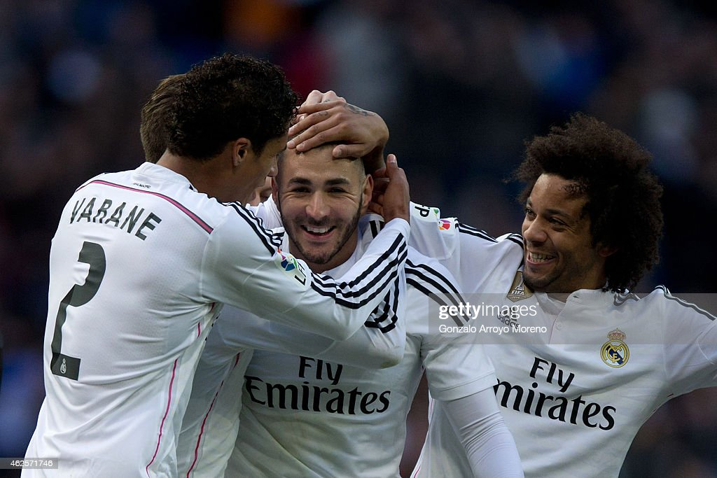 Karim Benzema of Real Madrid CF celebrates scoring their fourth goal with teammates Raphael Varane and Marcelo during the La Liga match between Real...